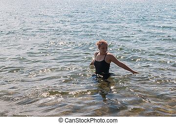 Girl With Raised Arms in the Water at the Beach