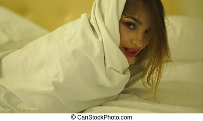 beautiful young girl with red lips in a white blanket on the bed