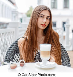 Beautiful young girl with red lips rests in a cafe on a sunny day.