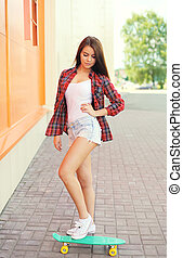 Beautiful young girl with skateboard posing in city