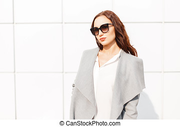 Beautiful young girl with sunglasses in a gray coat on a sunny day