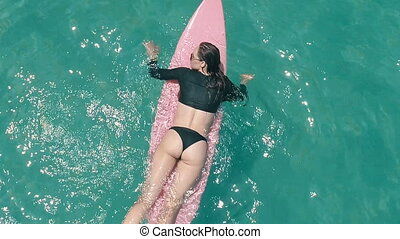 Beautiful young girl with surfboard in the sea water -...