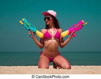 Beautiful young girl with water gun
