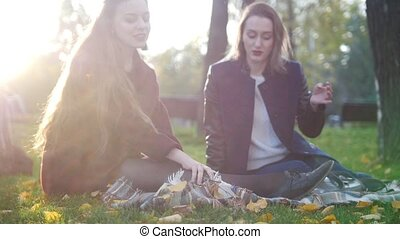 Beautiful young girls at picnic , laying down on the blanket...