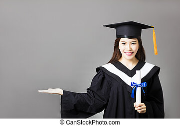 beautiful young graduate holding diploma with showing gesture