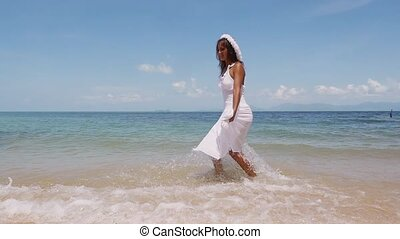 Beautiful young happy woman in a white dress and flower wreath runs along the seacoast barefoot in the sea and enjoys herself. Beach with white sand. Slow Motion. 1920x1080