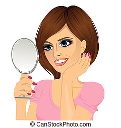 beautiful young happy woman looking at herself in small mirror