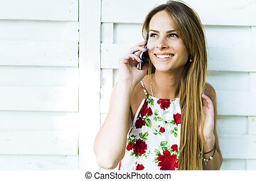 Beautiful young happy woman smiling during a phone call ...