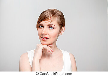 Beautiful young happy woman with make-up poses in studio