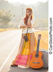 Beautiful young hippie girl using mobile phone on the country road