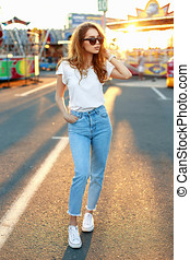 Beautiful young hipster girl in sunglasses in a white T-shirt, vintage jeans and white sneakers walking in the amusement park at sunset.