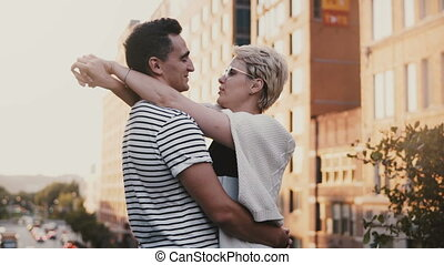 Beautiful young Hispanic man and European woman standing and hugging on a New York sunset bridge sharing a date night.
