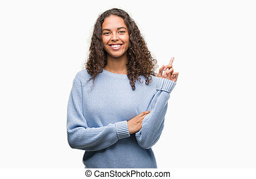 Beautiful young hispanic woman very happy pointing with hand and finger to the side