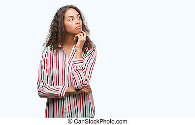 Beautiful young hispanic woman with hand on chin thinking about question, pensive expression. Smiling with thoughtful face. Doubt concept.