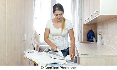 Beautiful young housewife ironing clean clothes in laundry -...