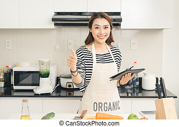 Beautiful young housewife woman with tablet computer cooking in a kitchen