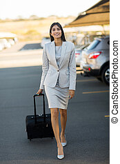 young indian businesswoman walking in airport parking lot