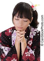 Beautiful young japanese girl praying, closeup portrait.