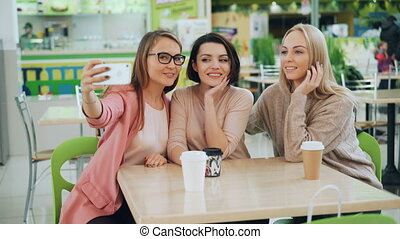 Beautiful young ladies are taking selfie using smartphone sitting at table in cafe and posing with drinks. Friendship, leisure time and modern technology concept.