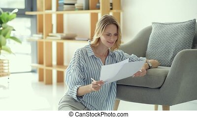 Beautiful young lady checking business documents at home -...