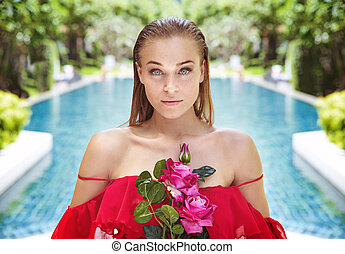 Beautiful young lady holding a bouquet of roses
