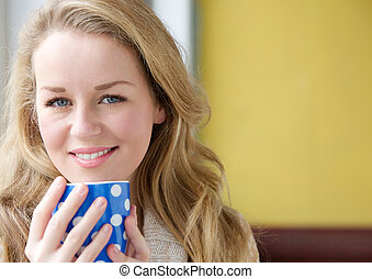 Beautiful young lady holding tea cup at home