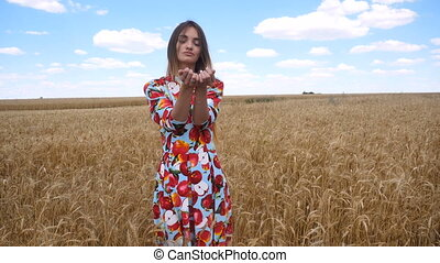 young lady in a dress standing in a field and looking at the wheat spikelet in Palms