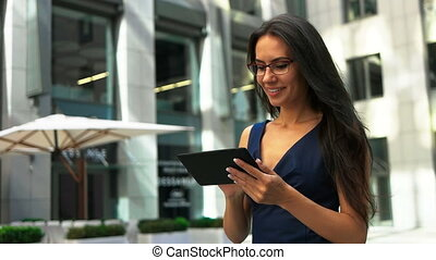 Beautiful young lady in glasses holding a tablet on hands, walking on the street.