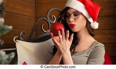 beautiful young lady in glasses in santa hat having fun with christmas tree ball and smiling
