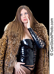 Beautiful young lady in latex suit and a fur coat