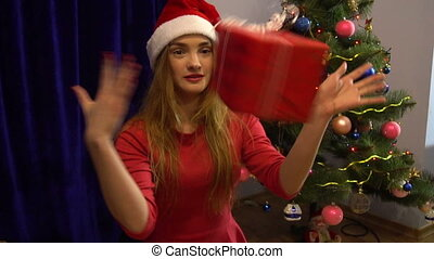 beautiful young lady in santa hat having fun with christmas gift and smiling