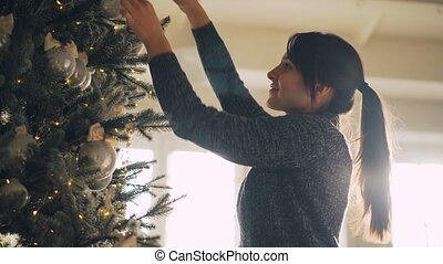 Beautiful young lady in sweater is decorating New Year tree with stylish decorations balls and lights hanging accessories on branches. People and events concept.