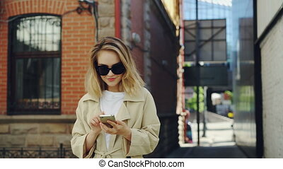 Beautiful young lady is holding smartphone and using it walking along street in modern city. Technology, beautiful happy people and youth lifestyle concept.