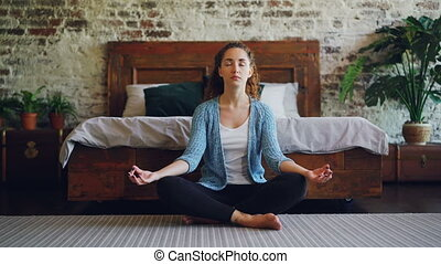 Beautiful young lady is sitting in lotus position on bedroom...