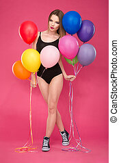 Beautiful young lady posing with balloons on pink background