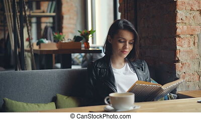 Beautiful young lady reading book in cafe enjoying...