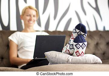 Beautiful young lady sitting on sofa, using laptop