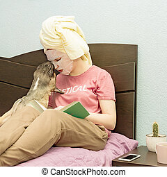 Beautiful young lady sitting on the bed, enjoying beauty procedures at home. Woman applying a face sheet mask, and reading a book. Paying with her French bulldog