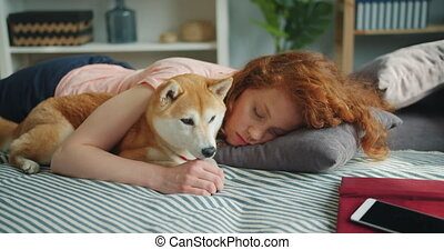 Beautiful young lady sleeping on couch at home hugging...