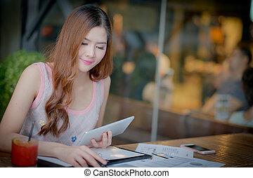Beautiful young lady with tablet sitting at the summer...