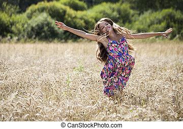 Beautiful young little girl running summer field