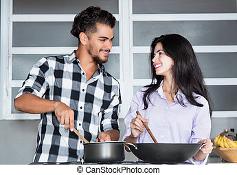 Beautiful young love couple cooking at kitchen