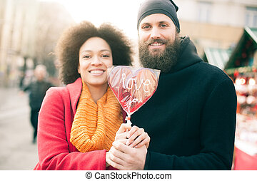 Beautiful young lovers holding a big red heart