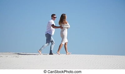 Beautiful young loving couple and walking barefoot in the desert