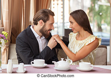 Beautiful young loving couple is dating in cafe