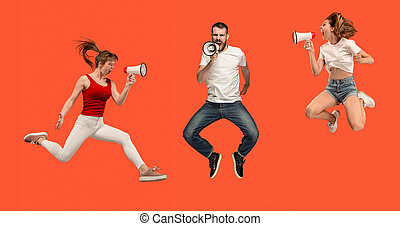 Beautiful young man and woman jumping with megaphone isolated over red background