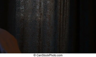 Beautiful, young man unveil curtain. Slow motion