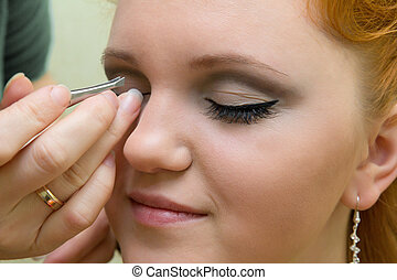 beautiful young model getting fashion make-up and eyelash extension