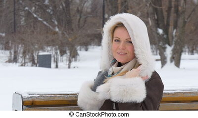 Beautiful young model on the photo shoot, smiling. Winter snowstorm.
