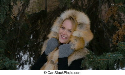 Beautiful young model participating in a photo shoot in the woods in winter. She looks at the camera smiling.